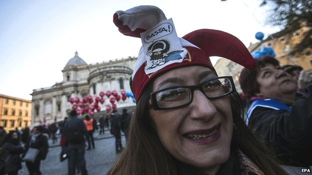 "A demonstrator wears a hat saying ""Enough!"" as she takes part in a rally in Rome - 12 December 2014."