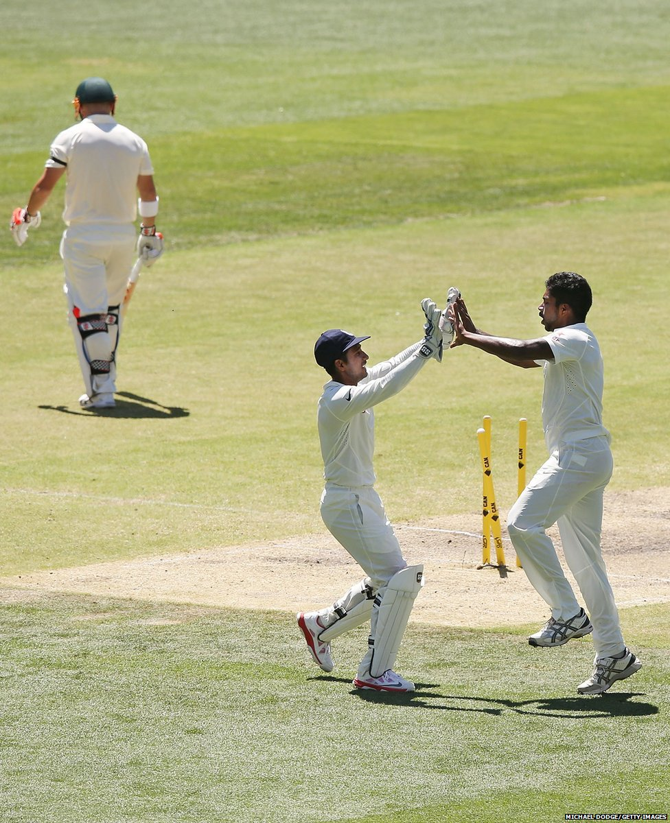 Varun Aaron of India (right) celebrates with Wriddhiman Saha