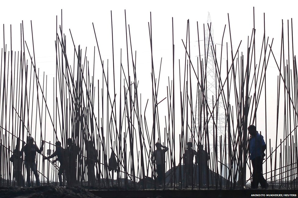 Labourers help construct a bridge over the River Yamuna for a rail project in Delhi