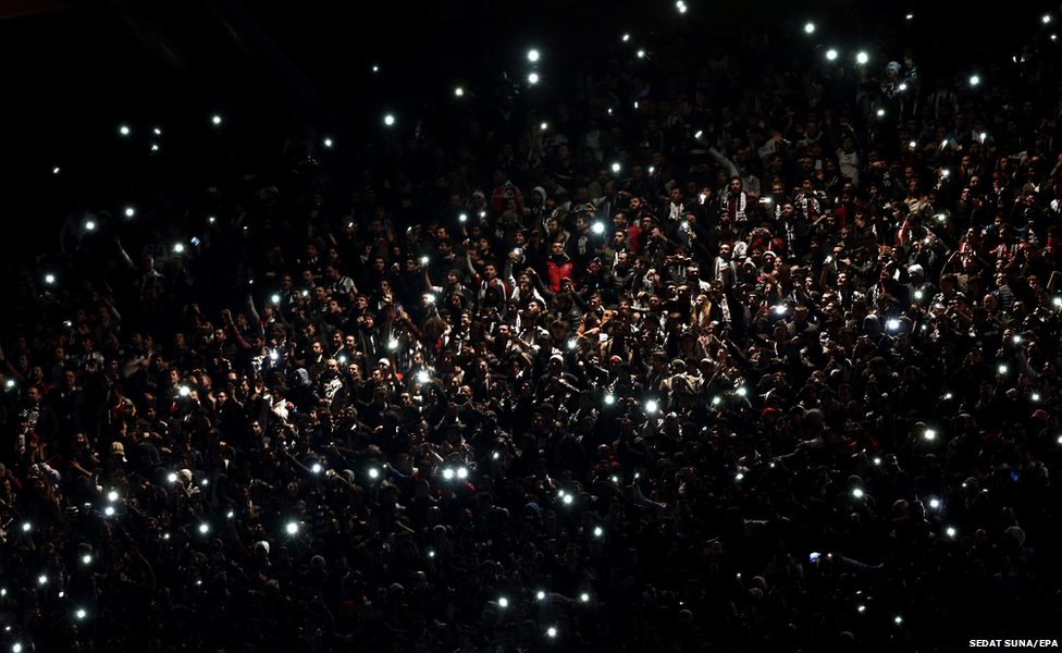 Fans hold mobile phones up during a power cut in the game between Tottenham Hotspurs and Besiktas