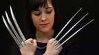 "A Christies auction house staff poses with a pair of ""adamantium"" claws"
