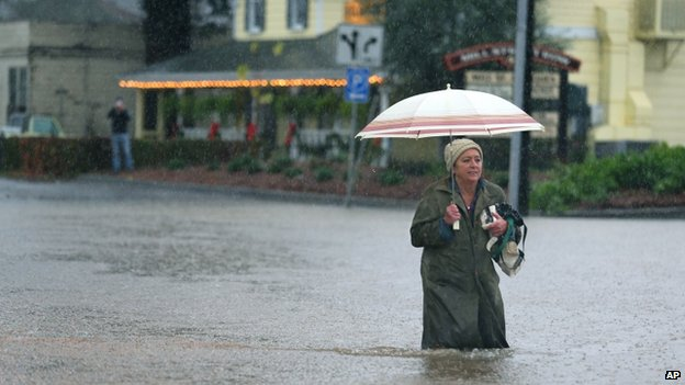A woman makes her way through floodwaters in Healdsburg, California