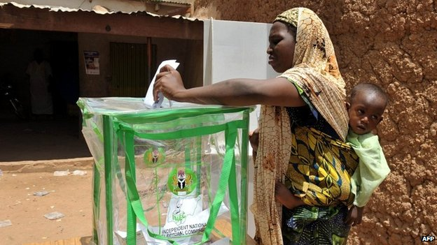 A Nigerian woman carrying her baby casts her vote at a polling station in Nigeria's presidential elections - 16 April 2011