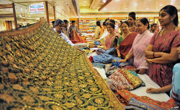 Women look at a display of saris at a wedding collection in Hyderabad