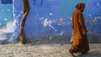 A person walking in a street in Chefchaouen