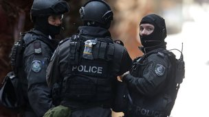 Armed policeman talk on Phillip St close to Martin Place on December 15, 2014 in Sydney, Australia