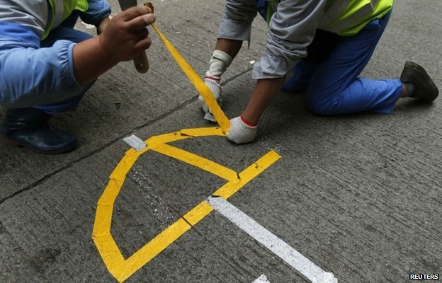 "Workers remove a logo left by pro-democracy protesters in the shape of an umbrella during a clearance at the last ""Occupy"" protest site blocking a main road at Causeway Bay shopping district in Hong Kong"