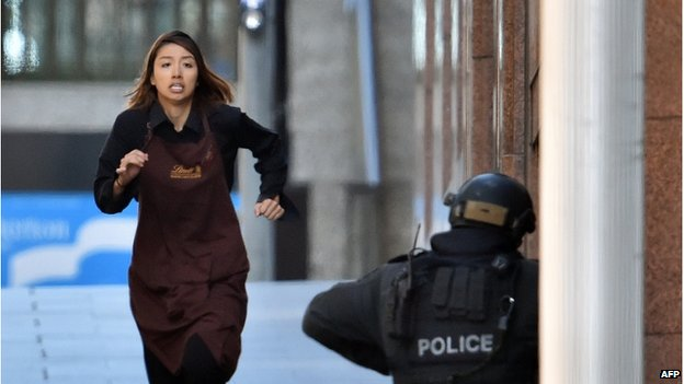 One of the hostages runs towards police from a cafe in the central business district of Sydney on 15 December 2014
