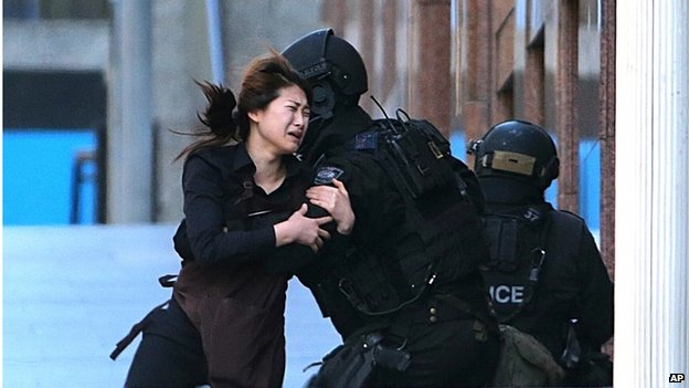 A hostage runs to armed tactical response police officers for safety after she escaped from a cafe under siege at Martin Place in the central business district of Sydney, Australia, Monday, 15 December 2014