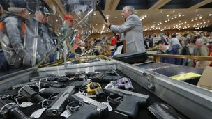 In this Saturday, Jan. 26, 2013 file photo, handguns appear on display at the table of David Petronis of Mechanicville, N.Y., standing with rifle,