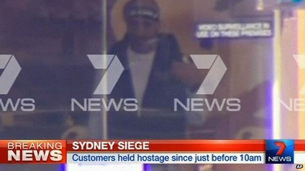 This image taken from video shows a man believed to be the gunman, Man Haron Monis, inside a cafe in Sydney, Australia Monday, Dec. 15, 2014.