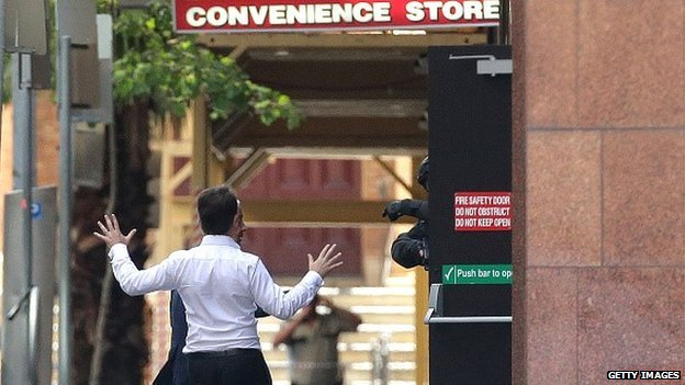 Two hostages run to safety outside the Lindt Cafe, Martin Place on December 15, 2014 in Sydney, Australia