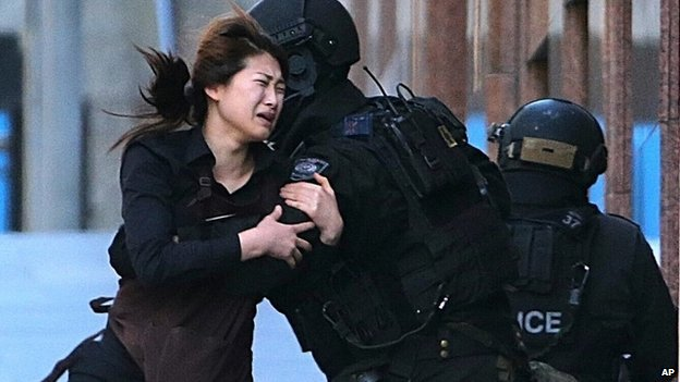 A hostage runs to armed tactical response police officers for safety after she escaped from a cafe under siege at Martin Place in the central business district of Sydney, Australia, Monday, Dec. 15, 2014.