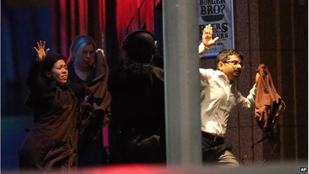 Hostages run towards armed tactical response police as they run to freedom from a cafe under siege at Martin Place in the central business district of Sydney, Australia, Tuesday, Dec. 16, 2014.
