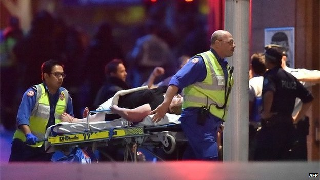 An injured hostage is carried out of a cafe in the central business district of Sydney on December 16, 2014.