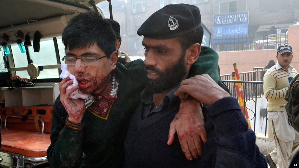 A security guard helps a student after a gun attack at a school in Peshawar