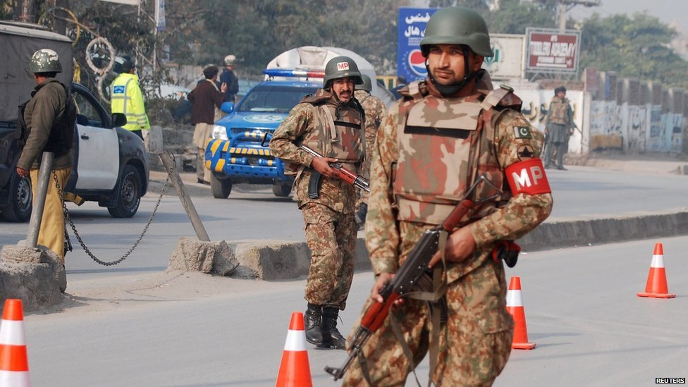 Pakistani army troops guard a road near an armed incident in Peshawar