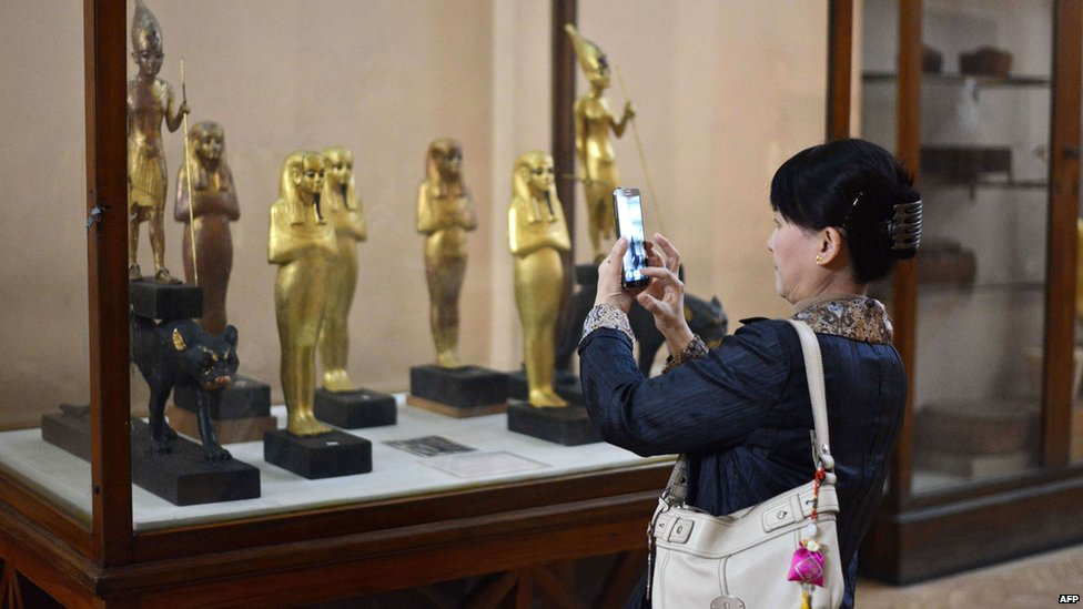 Woman taking photo of statues in case