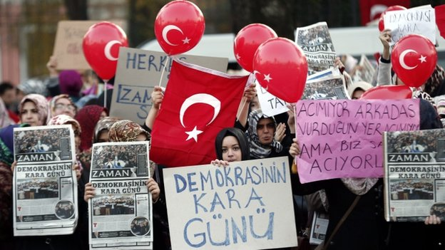 Supporters of the Hizmet movement take part in a demonstration after Turkish police began an operation targeting sympathetic media in Istanbul