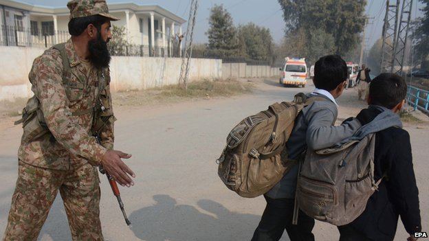 Children being ushered away from the scene of a gun attack in Peshawar