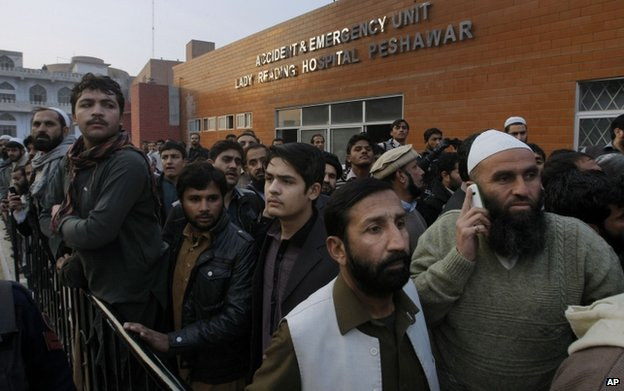 Relatives wait outside a hospital in Peshawar, 16 December