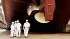 DNV GL staff inspecting the underside of a ship in dry dock