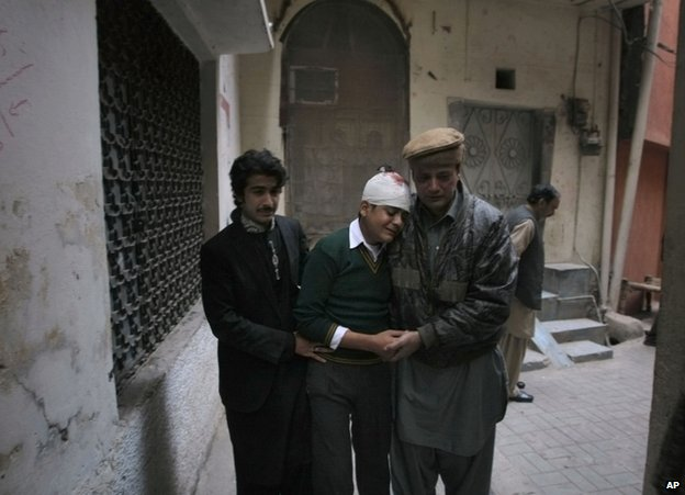 Relatives comfort injured student Mohammad Baqair in Peshawar, 16 December