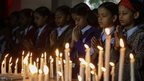 Indian school children observe two-minutes of silence and light candles to pray for the victims who were killed in an attack at the Army run school in Peshawar, Pakistan, during a memorial ceremony in Mumbai, India, 17 December