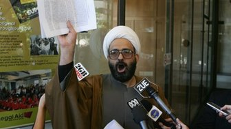 A picture made available 15 December 2014 shows Muslim cleric Man Haron Monis speaking to the media after leaving court after he had been charged with seven counts of unlawfully using the postal service to menace in Sydney on 10 November 2009