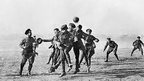 Soldiers playing football during World War One
