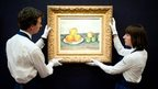 Sotheby's employees pose in front of 'Les Pommes' by Paul Cezanne