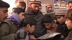 Two men and a group of children in Peshawar, Pakistan, gathered together to look at a newspaper reporting Taliban school attack