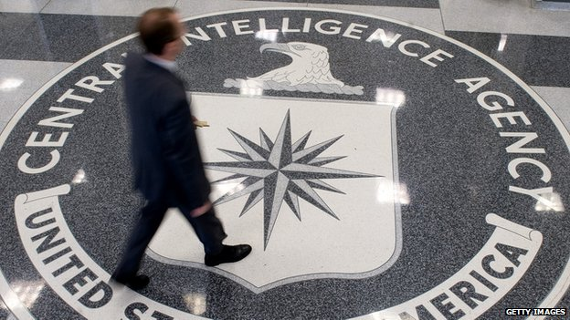 A man walks across the seal of the Central Intelligence Agency at its Virginia headquarters.