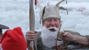 A swimmer in a Father Christmas costume at a festive swim in Cornwall