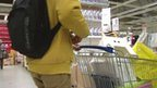Shopper with trolley full of goods