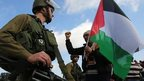 A protester holds Palestinian flag in front of Israeli soldier during protest against Jewish settlements between Jerusalem and Jericho. 28 Nov 2014