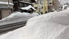Head-high snowdrifts by roadside in Tsunan, Niigata Prefecture Japan