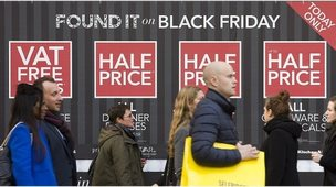 Shoppers in front of Black Friday sign