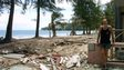 John stands by the devastated beach strewn with rubbish.