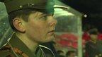 Boy dressed in World War One soldier uniform watching football match