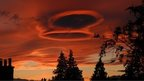 Bright orange sky with two unusual and prominent circular clouds.