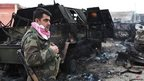 Kurdish fighter next to vehicle destroyed by IS during advance towards Mount Sinjar. 18 Dec 2014