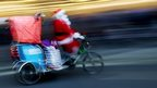Father Christmas doing the rounds by bike
