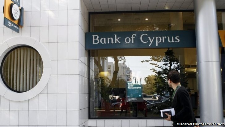 A  man walk outside a branch of Bank of Cyprus in Nicosia