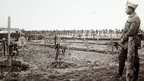 WW1 soldier standing next to graves