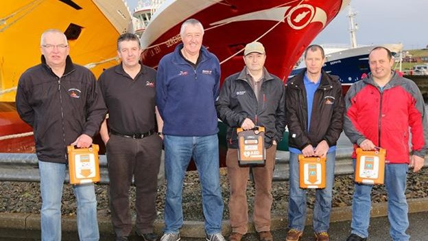 Fishermen with defibrillators in front of boats