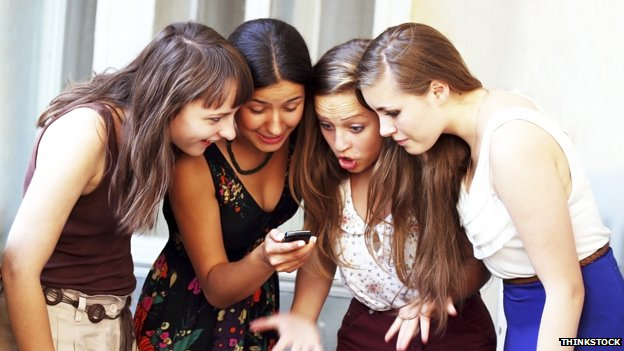Girls corwded around a mobile phone