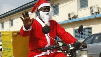Jumia delivery men dressed as Santa Claus drive their motorcycles to deliver goods to customers in Abidjan, Ivory Coast - Thursday 18 December 2014