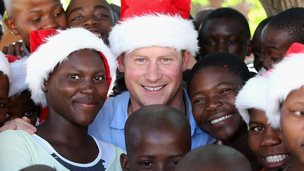 Prince Harry with children wearing Santa hats