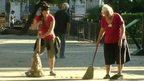 women sweeping the street